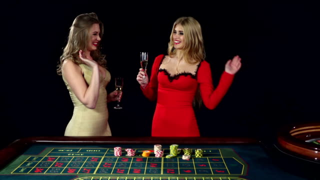 Two girls celebrating the victory in roulette. Black video