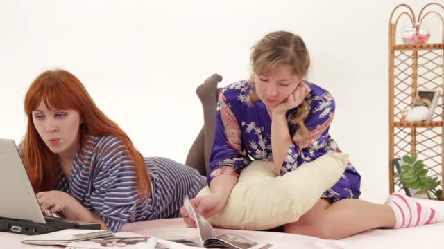 two girls choose a dress - ligga på mage bildbanksvideor och videomaterial från bakom kulisserna