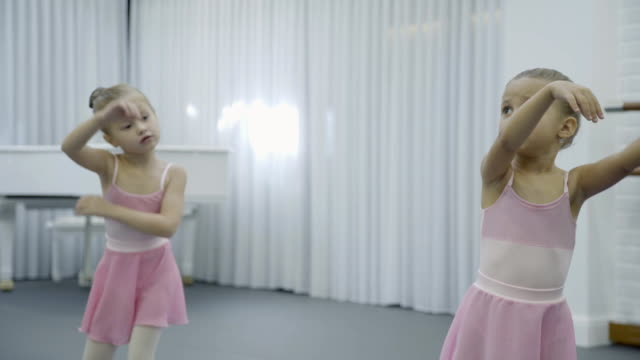Two girls do the trunk turnings with rasing hands during the ballet class video