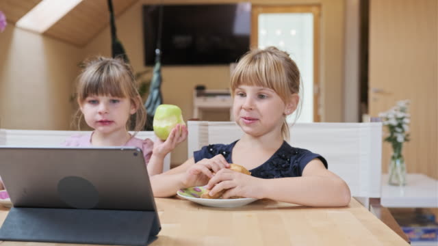 Twee meisjes genieten van ontbijt tijdens het kijken naar cartoons video