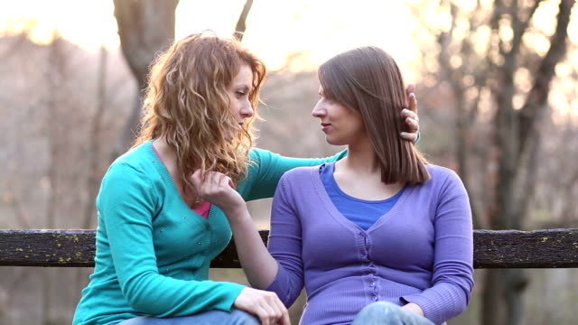 two girls flirting in park - same sex couples stock videos and b-roll footage