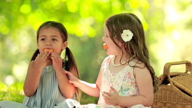 Two girls have fun eating fruit video