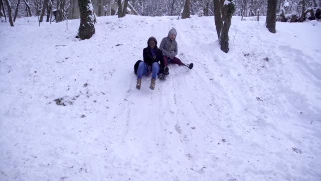due ragazze si divertono sulla neve,tobogganing - scivolare video stock e b–roll