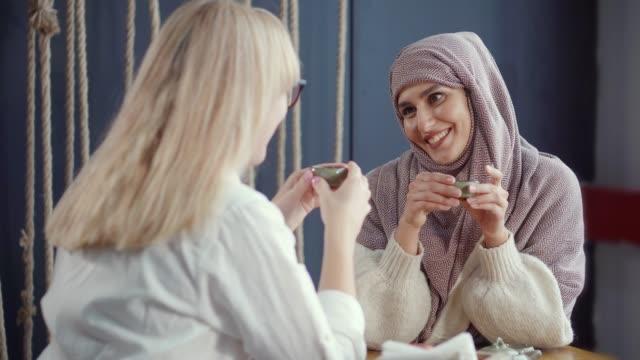 två flickor som har en härlig prat inomhus över te. - anständig klädsel bildbanksvideor och videomaterial från bakom kulisserna