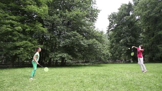 Deux filles s'amusant et en jouant une partie de badminton à l'extérieur dans un parc - Vidéo