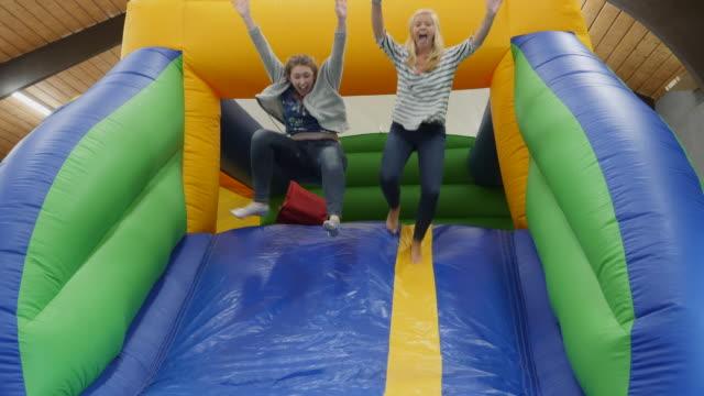 vídeos de stock, filmes e b-roll de 4k: duas meninas se divertindo em um castelo bouncy inflável slide - inflável