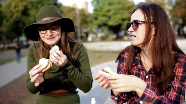 vídeos de stock e filmes b-roll de two girls hipster eating sandwiches in the park, laugh and talk. stay in the park. the holiday sandwich. - sanduíche