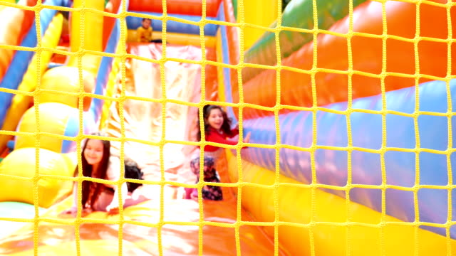 Two girls holding on the net of inflatable rubber castle playground. Recreation outdoors for kids video