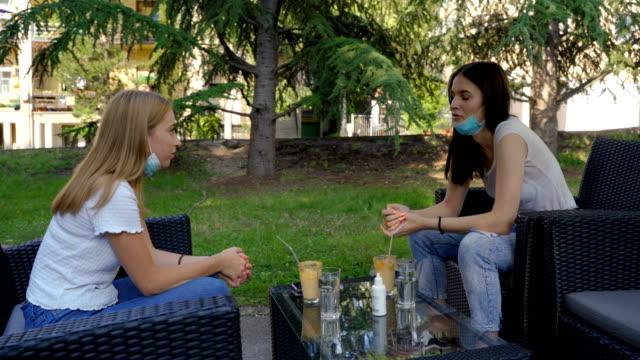 due ragazze in caffetteria in corona virus pandemia - terrazza video stock e b–roll