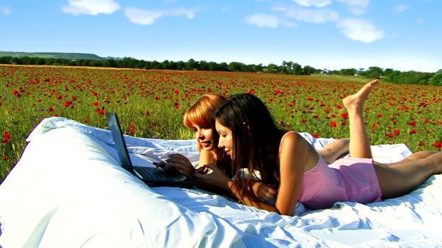 Two girls in poppy field with laptop video