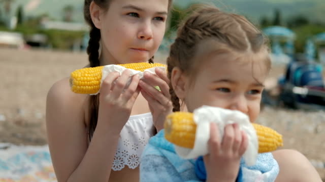 Two girls in the summer eat boiled corn in a napkin video