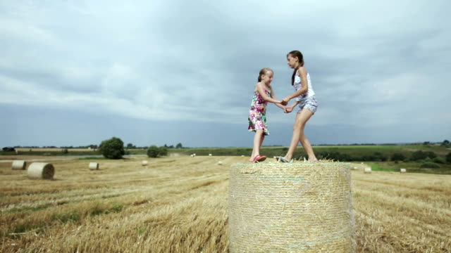 Two girls jump on haystack. video