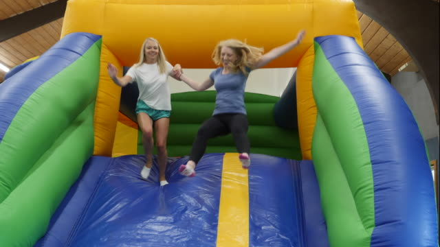 4k Two Girls Jumping On A Bouncy Castle Inflatable Slide Stock Video -  Download Video Clip Now - iStock