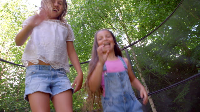 Two Girls Jumping On Trampoline Shot In Slow Motion video