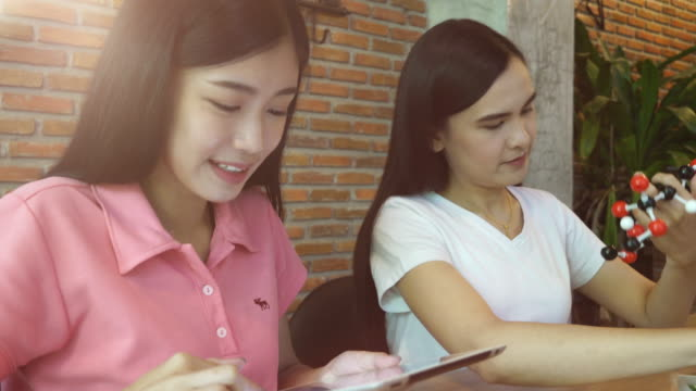Two girls learning on chemistry subject video