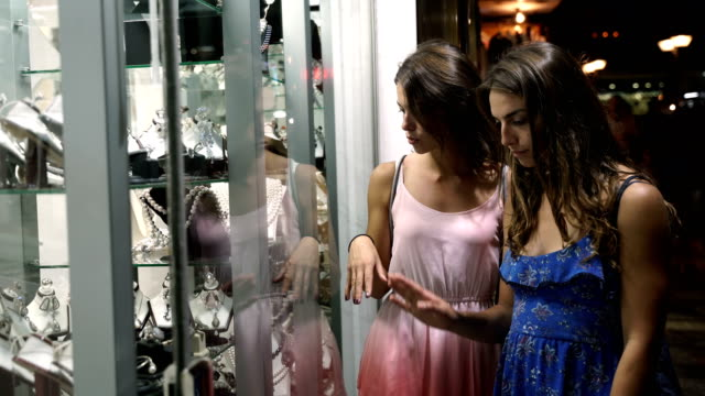 Two girls looking in the shop window with jewelry