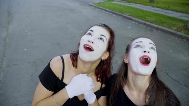 two girls mimes imitate embarrassment when see camera - гримировальные краски стоковые видео и кадры b-roll