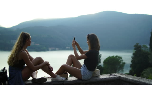 Two girls on stone wall taking pictures with smartphone, view of lake and mountains below