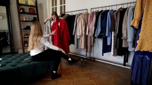 Zwei Mädchen oder Zwillingsschwestern beim gemeinsamen Einkaufen: Langhaarige junge blonde Hündin versucht einen neuen grauen und roten Mantel, während sie in der Nähe der Regale mit verschiedenen Outfits auf Kleiderbügeln stehen. Besprechen Sie ihre  – Video