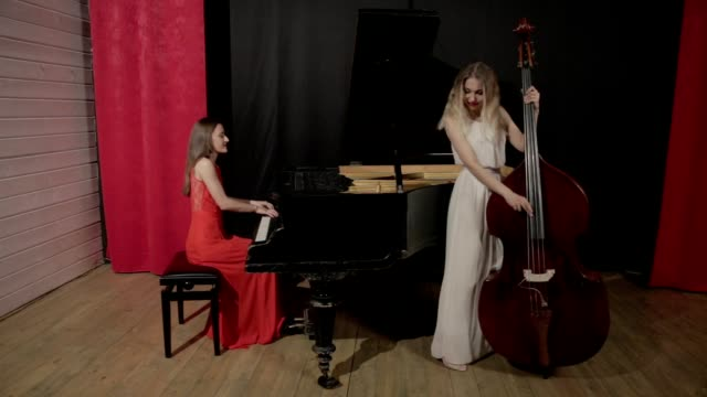 Two girls playing musical instruments. Piano and doublebass video