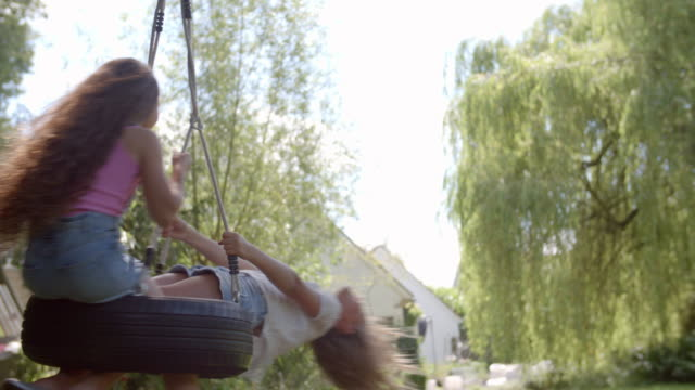 Two Girls Playing On Tire Swing In Garden video