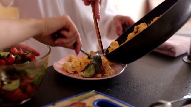 Deux jeunes filles préparent le petit déjeuner à la maison dans la cuisine - Vidéo