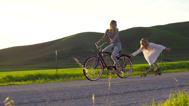 Two Girls Riding Bike And Skateboard Down Hill At Sunset