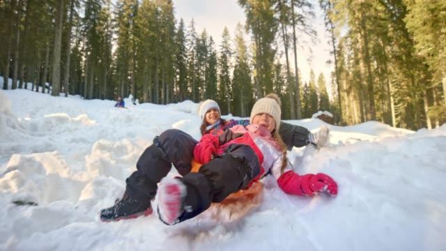 slo mo två flickor rider sin plast slädar nedför en snöig backe och skrattar - snow kids bildbanksvideor och videomaterial från bakom kulisserna