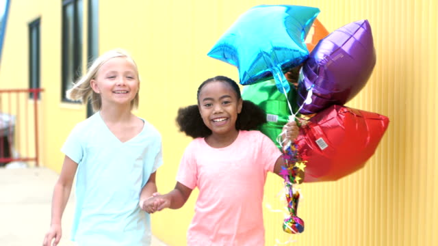 Two girls running by with balloons, holding hands video