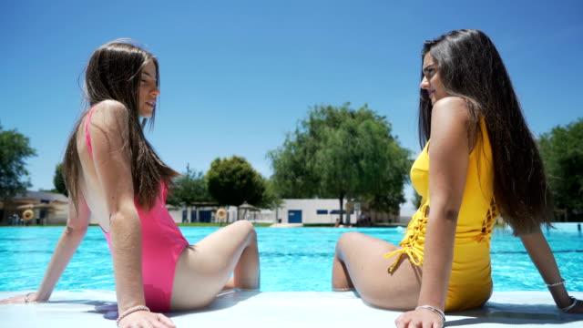 zwei mädchen sitzen im schwimmbad entspannt - sun chair stock-videos und b-roll-filmmaterial