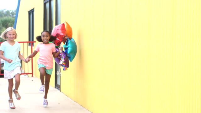 Two girls skipping by with balloons, holding hands video