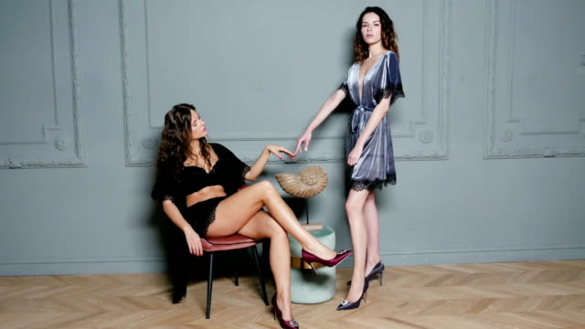 two girls stand in light coats in the studio and lean their fingers - część ciała zwierzęcia filmów i materiałów b-roll