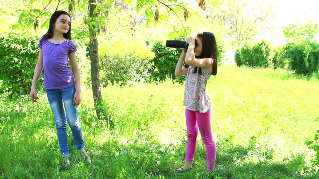 Two girls taking pictures in the city park video