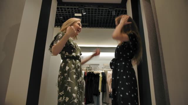 vídeos de stock e filmes b-roll de two girls tried on new dresses in fitting room - amizade feminina