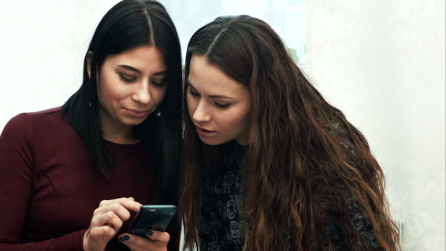 Two girls use a smartphone, talking, smiling, sitting on sofa video