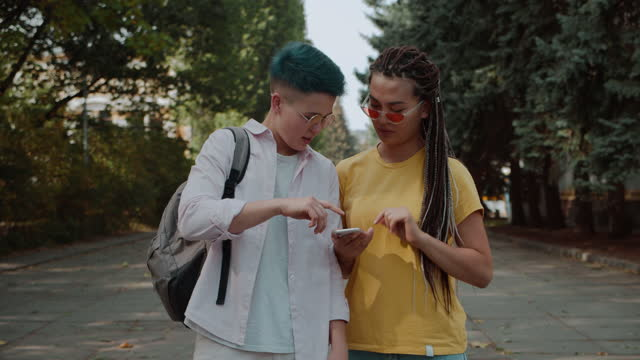 Two girls using navigation app on smartphone to find destination in city, travel