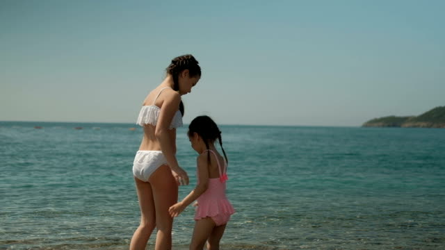 Two girls walk on water by sea on summer day outdoors video