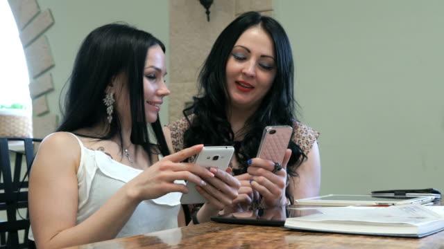 två flickor titta på bilder på en mobiltelefoner - två människor bildbanksvideor och videomaterial från bakom kulisserna