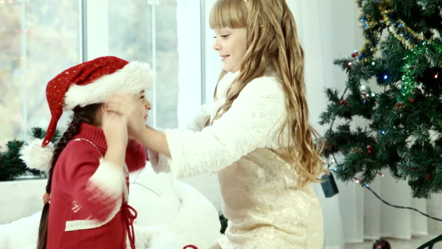 Two girls wear Santa hats to one another video