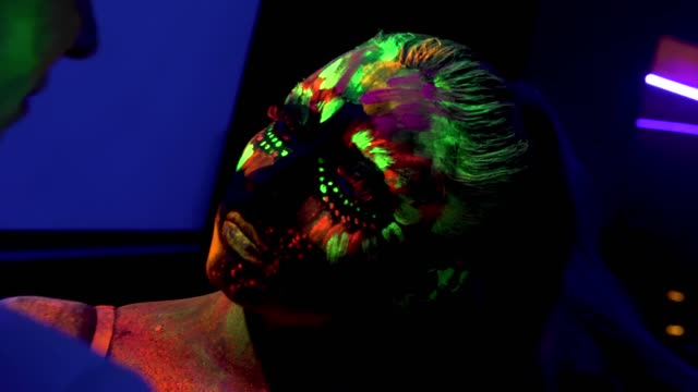 Two girls with fluorescent make-up, body art design in UV, painted colorful faces video