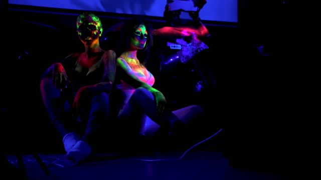 Two girls with futuristic fluorescent bodyart in ultraviolet light in night club
