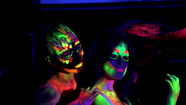 Two girls with futuristic fluorescent bodyart in ultraviolet light in night club video