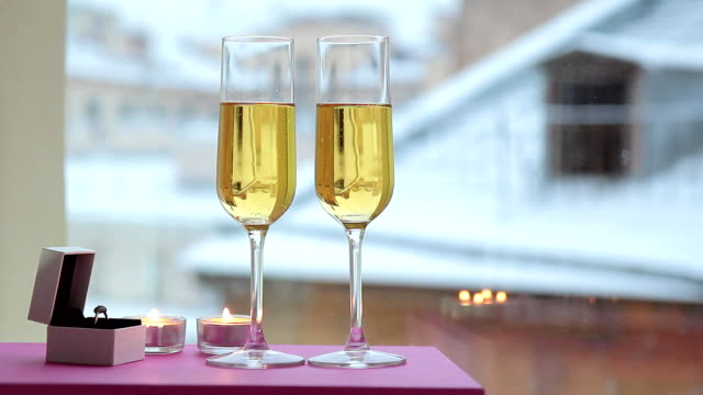 Two glasses champagne and candles on table by window indoor video