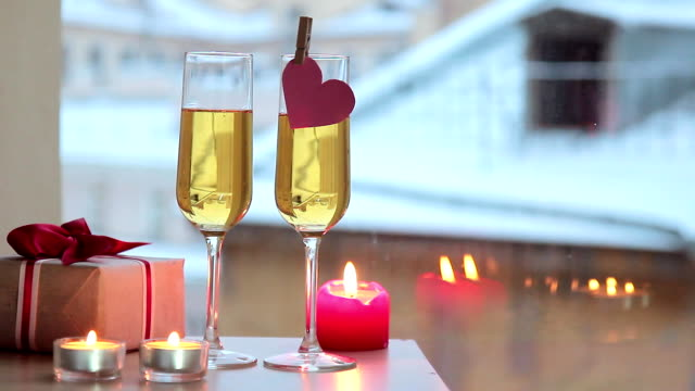 Two glasses champagne candles and box on table by window indoor video
