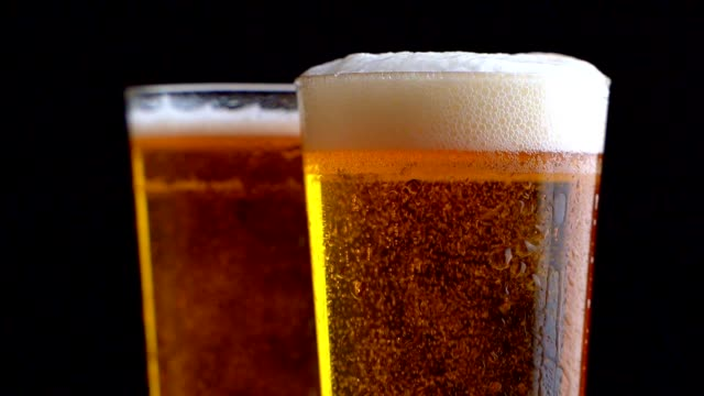Two glasses full of beer on table with black background Two glasses full of beer on table with black background. lager stock videos & royalty-free footage
