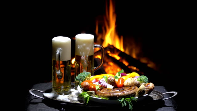 two glasses of beer on the background of fire two glasses of beer on the background of fire lager stock videos & royalty-free footage