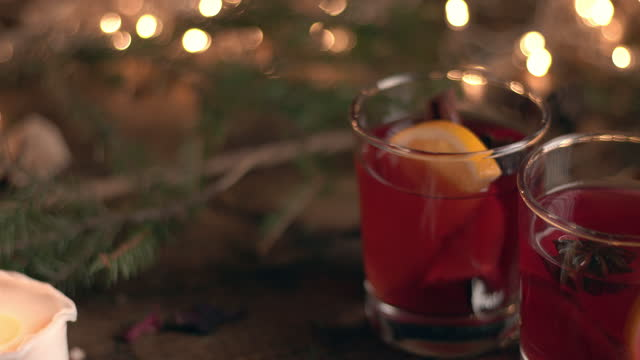 Two glasses of mulled wine on a background of fir branches and burning candles