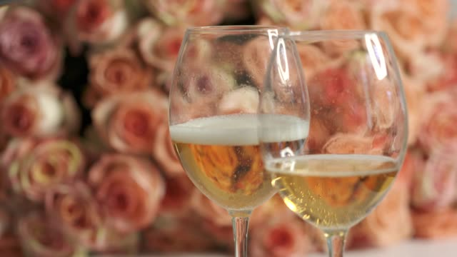 Two glasses of sparkling wine and large bouquet of pink roses