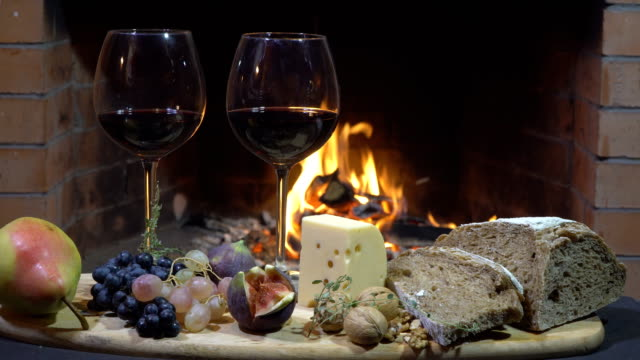 Two glasses of wine, cheese, bread and fruit on fire background, dolly shot Two glasses of wine, cheese, bread and fruit on fire background, dolly shot chalet stock videos & royalty-free footage