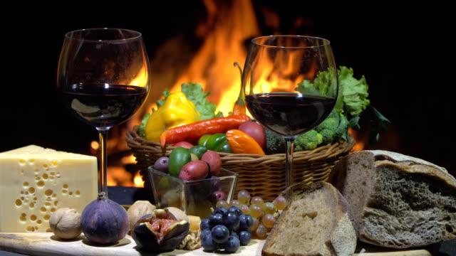 ワイン、チーズ、パン、ドリー ショット火災の背景にフルーツを 2 杯 - 花壇点の映像素材/bロール